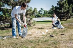 Happy positive man cleaning rubbish. Eco project. Happy positive nice men holding a plastic bag and cleaning rubbish while participating in eco project Royalty Free Stock Image