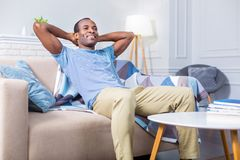 Happy positive man resting at home. Such a pleasure. Happy positive nice man sitting on the sofa and smiling while resting at home Royalty Free Stock Photo