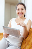 Happy  mature woman reads newspaper Royalty Free Stock Photo