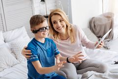 Happy positive mother hugging her son. Family entertainment. Happy positive loving mother sitting on the bed and holding a tablet while hugging her son royalty free stock photo