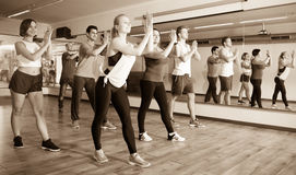 Happy positive people learning zumba steps. In dance hall Stock Photo