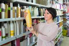 Happy positive pleasant woman choosing hair care products. In shop and smiling stock photo