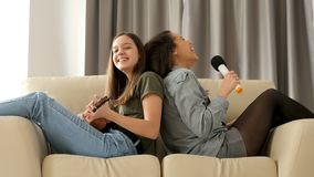 Happy and positive sisters playing and singing on the sofa. In the living room. The youngest is playing at ukulele while the oldest is singing in a microphone stock video footage