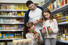 Happy  positive smiling parents with little girl buying tinned Royalty Free Stock Photo
