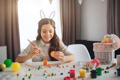 Happy positive teenager preparing for Easter. She sit alone at table and painting eggs. Girl smile. She wear rabbit ears stock photography