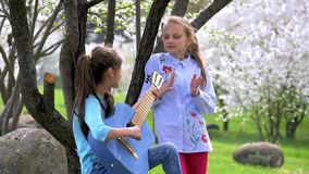 Happy and positive two school girlfriend playing music and singing in nature Park. one young girl plays guitar other claps her han. Happy and positive two school stock footage