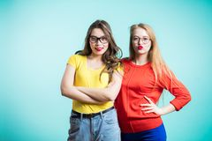 Happy positive two stylish girls hugging stand near the blue wall. Close up portrait funny joyful attarctive young women. Communication and friendship concept Royalty Free Stock Photos