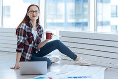 Happy positive woman holding a cup with coffee. Coffee at work. Happy positive beautiful woman holding a cup of coffee and smiling while working on the laptop Royalty Free Stock Image