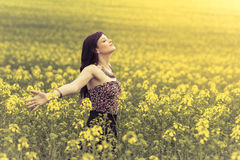 Happy positive woman in sunny summer love of youth freedom. Attractive genuine young girl enjoying the warm summer sun in a wide green and yellow meadow Stock Images