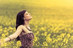 Happy positive woman in sunny summer ocean of yellow flowers. Attractive happy young girl enjoying the warm summer sun and her health in a wide green and yellow Royalty Free Stock Images