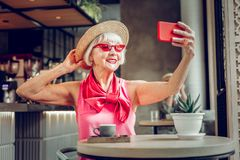 Happy positive woman taking a selfie on her phone stock images