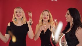 Happy positive women with glasses of champagne dancing on red background. stock video