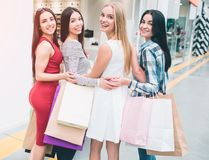 Happy and positive women are standing together and posing. They are looking back on camera and smiling. Also they have. Many bags in their hands. Girls had royalty free stock photography