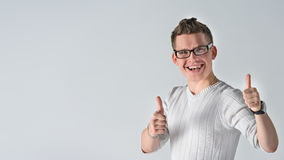 Happy positive young guy showing thumb up. Portrait of a smiling casual spectacled man showing two thumbs up and looking at camera over gray background. Man Stock Image