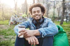 Happy and positive young male student with afro-hairstyle in trendy clothes sitting in park while smiling broadly and. Drinking coffee. Boyfriend suggest to Stock Images