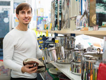 Happy positive young man buying new metallic pan Stock Image