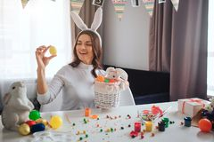 Happy positive young woman prepare fo Easter alone. She sit at table in room and hold yellor egg. Basket in front. She stock image