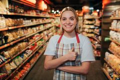 Happy positive young woman stand in line in grocery store. She look on camera and smile. Model keep big thumb up. royalty free stock images