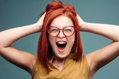 Happy and positivity red haired woman in eyeglasses shouting holding head by hands. Front view of happy and positivity red haired woman in eyeglasses shouting stock image