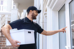 Happy postman with package waiting for customer Stock Photos