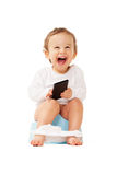 Happy potty training. Laughing boy with smartphone sitting on the pot on isolated white stock images