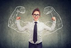 Happy powerful young business woman. Flexing her muscles showing strength stock image