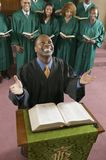 Happy preacher with Bible at church altar looking up high angle view Stock Photo