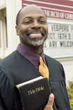Happy Preacher Holding Holy Bible. Portrait of happy preacher holding Holy Bible while standing in front of church Royalty Free Stock Photos