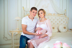 Happy Pregnancy: husband holding baby booties near the belly his pregnant wife Royalty Free Stock Photography