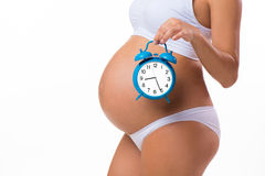 Happy pregnancy. Pregnant belly with alarm clock. Conceptual image. Soon birth. Fetal development by months Royalty Free Stock Images
