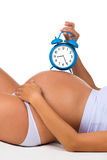 Happy pregnancy. Pregnant belly with alarm clock. Soon birth. Royalty Free Stock Photography