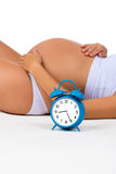 Happy pregnancy. Pregnant belly with alarm clock. Soon birth. Fetal development by months. ? Stock Image