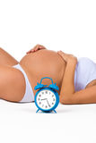 Happy pregnancy. Pregnant belly with alarm clock. Soon birth. Fetal development by months Royalty Free Stock Photos