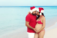 Happy pregnancy, pregnant family. Expectant parents in Christmas costumes and Santa hat on the sea Stock Photo