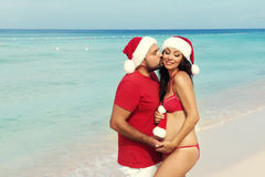 Happy pregnancy, pregnant family. Expectant parents in Christmas costumes and Santa hat on the sea Royalty Free Stock Photo