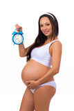 Happy pregnancy. Smiling pregnant woman holding alarm clock. Stock Photo