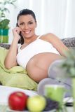 Happy pregnancy talking by cell phone Stock Photo