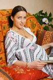 Happy pregnancy women. Sitting on sofa and reading book Royalty Free Stock Photography