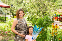Happy pregnant asian mom and child girl hugging. The concept of childhood and family. Royalty Free Stock Photos