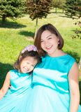 Happy pregnant asian mom and child girl hugging. The concept of childhood and family. Beautiful Mother and her baby outdoor stock photography