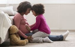 Free Happy Pregnant Black Woman And Her Cute Daughter Bonding At Home Stock Photo - 181446800