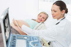 Happy pregnant blonde having an ultrasound scan. At the hospital Royalty Free Stock Images