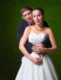 Happy pregnant bride and groom embracing belly together Royalty Free Stock Images