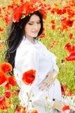 Happy pregnant brunette girl on poppy field Royalty Free Stock Photo