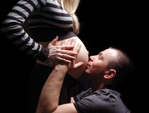 Happy Pregnant Couple. Man embraces and kisses a stomach of the pregnant woman Stock Photos