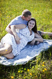 Happy pregnant couple. A young man kissing a  pregnant woman on a blanket in a field of yellow flowers Stock Image