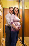 Happy pregnant couple. Happy couple at home entrance. Pregnant wife with her husband stock photo