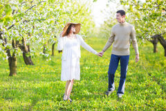 Happy pregnant couple in the blossom garden Royalty Free Stock Photo