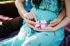 Happy pregnant couple. Close up hand with baby girl shoes Royalty Free Stock Images