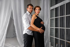 Happy Pregnant Couple dressed in black and white embrace each other by the window Stock Photography
